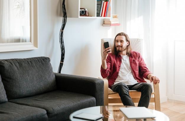 Улыбающийся молодой человек сидит и с помощью мобильного телефона в домашних условиях