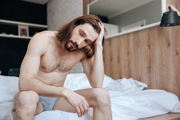 疲れて思慮深い若者に座ってベッドの上で考えて