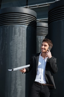 通りに電話で話しているドキュメントとハンサムな男