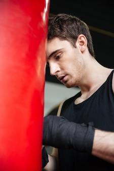 Утомленный человек боксер, опираясь на грушу