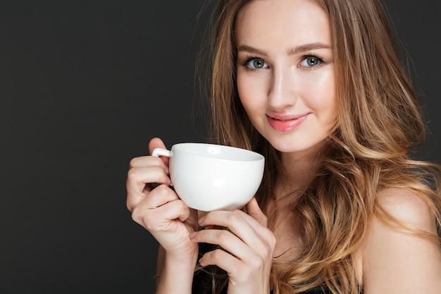 白いカップを押しながらコーヒーを飲みながら魅力的な若い女性を笑顔