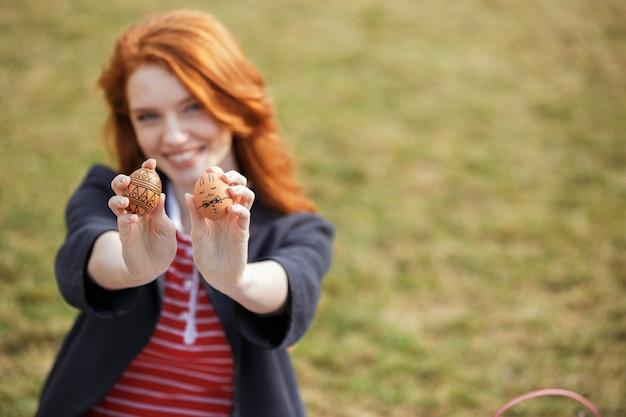 Женщина с длинными рыжими волосами показывает два окрашенных пасхальных яйца
