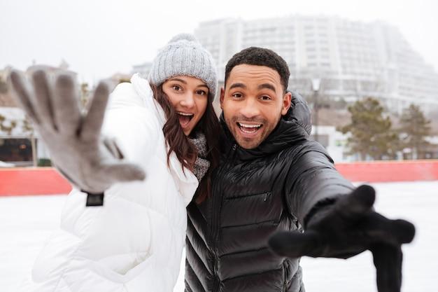 幸せな愛情のあるカップルが屋外アイススケートリンクでスケートします。