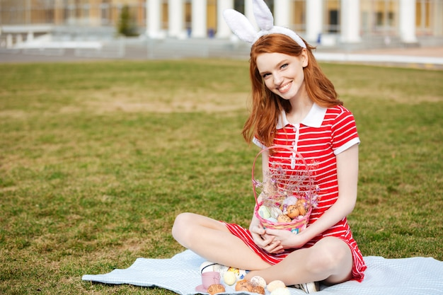 Улыбающаяся жизнерадостная женщина с длинными рыжими волосами в ушах зайчика