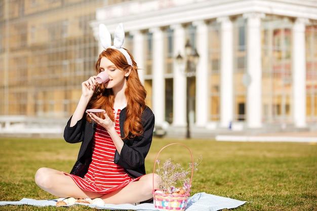 お茶のカップを保持している赤い頭の女性の肖像画