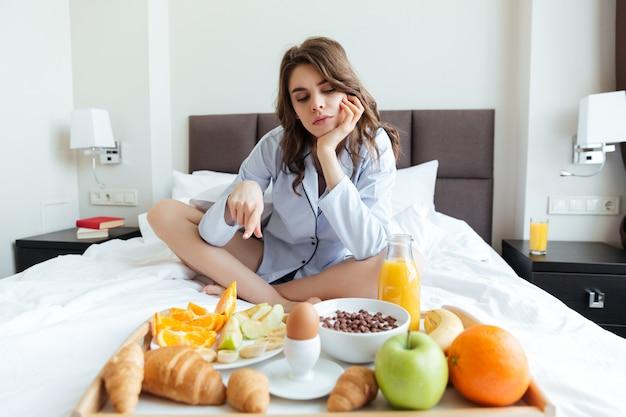 ベッドの上に座って、朝食付きのトレイを指す女性