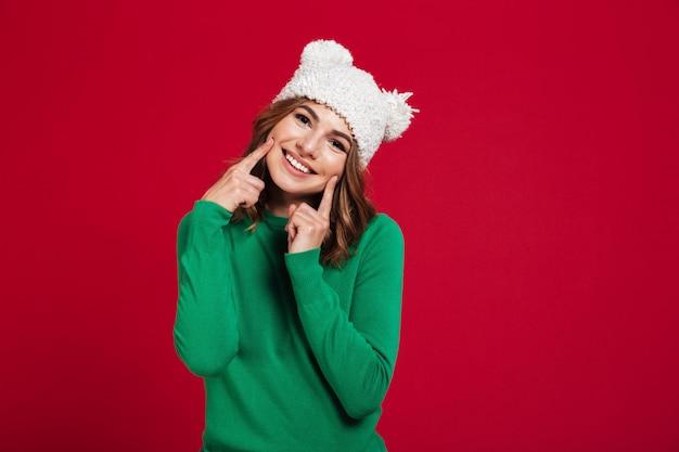 幸せな若いきれいな女性の帽子をかぶっています。