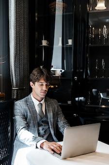 ラップトップコンピューターを使用してスーツでハンサムなビジネスマン