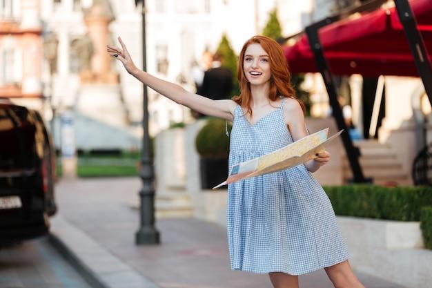 Молодая красивая женщина в платье держит карту путеводителя по городу