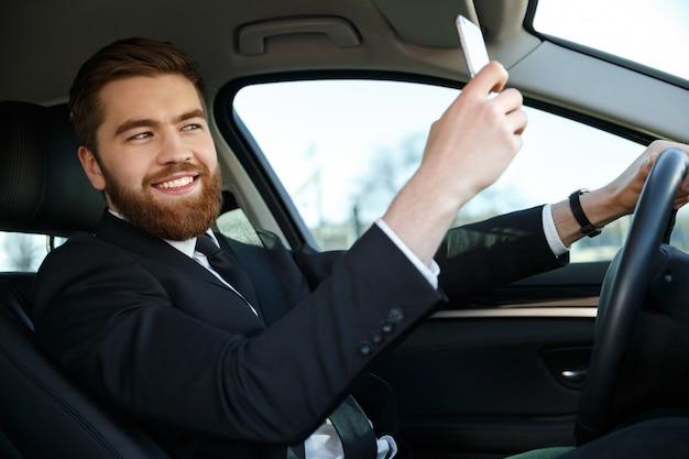 Вид сбоку улыбающийся деловой человек делает селфи