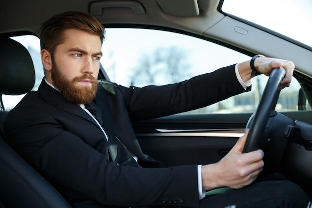 Серьезный концентрированный деловой человек в костюме за рулем своего нового автомобиля