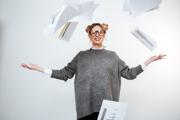 Усталая подчеркнутая женщина в очках бросает документы в воздух