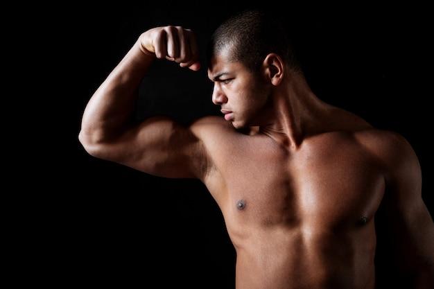 Красивый без рубашки человек фитнеса афроамериканца стоя и показывая бицепс
