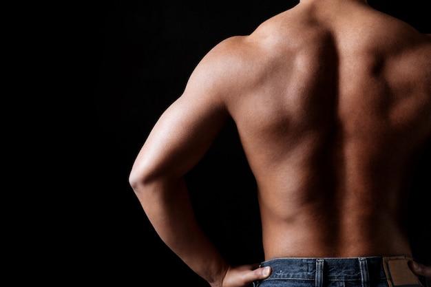 立っている筋肉運動若い男の背面図