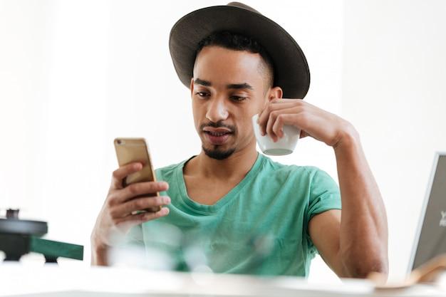 Африканский человек в футболке с помощью смартфона