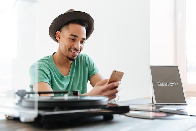 Молодой африканский человек в футболке с помощью смартфона