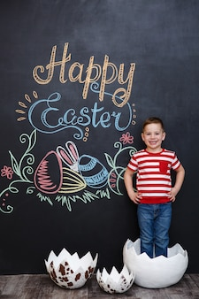 Счастливый маленький мальчик стоял внутри большой треснувшей яичной скорлупы