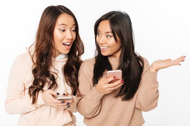 Азиатские довольно счастливые дамы сестры в чате по мобильным телефонам.