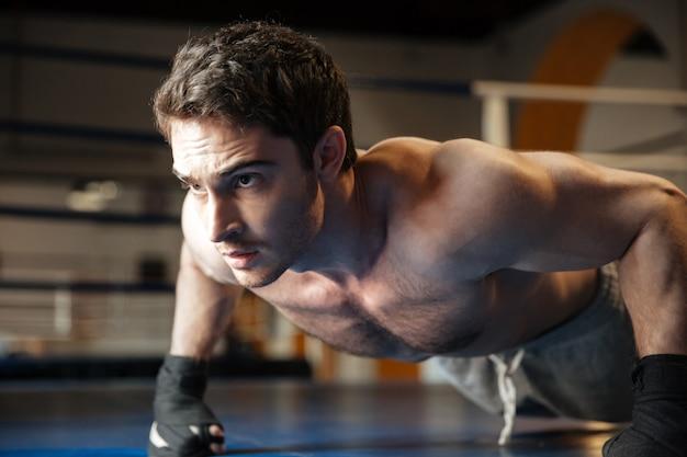 Крупным планом вид сбоку крутой боксер делает отжимания