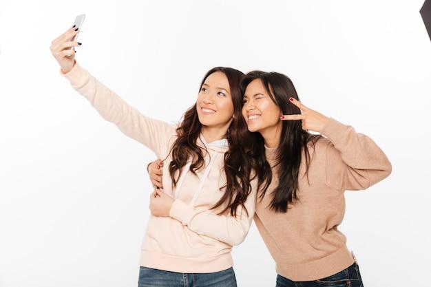 Две азиатские счастливые позитивные сестры