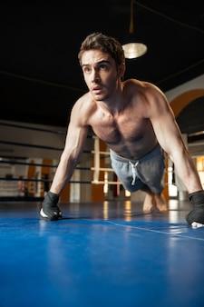Сильный человек толкает вверх во время тренировки