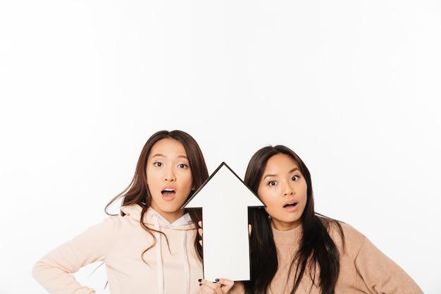 Азиатские дамы сестры держа стрелку.