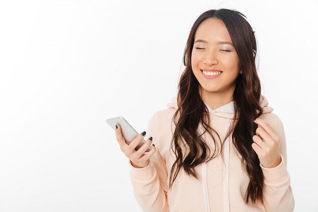 Музыка азиатской жизнерадостной женщины слушая с наушниками.