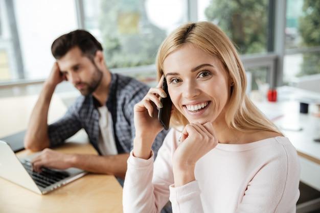 Два коллеги в офисе. женщина разговаривает по телефону.
