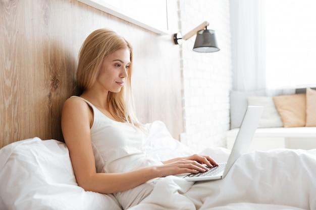Вид сбоку женщины на кровати с ноутбуком