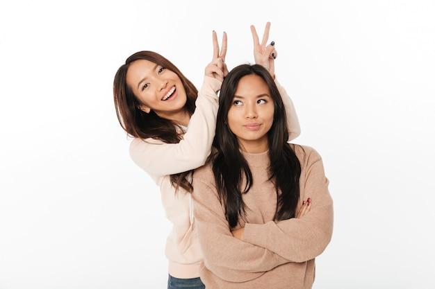 アジアのかわいい女性の姉妹は楽しい時を過します。