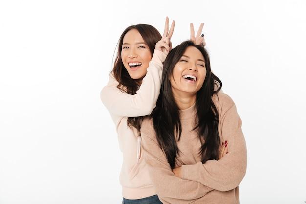 Азиатские милые сестры дамы весело проводят время.