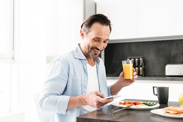 Счастливый зрелый человек, с помощью мобильного телефона во время завтрака