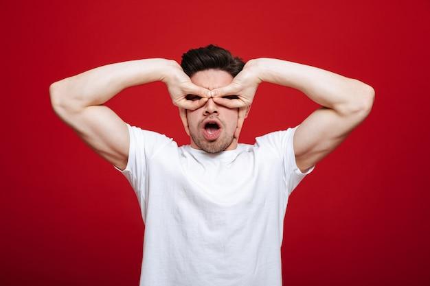 Портрет забавного молодого человека в белой футболке