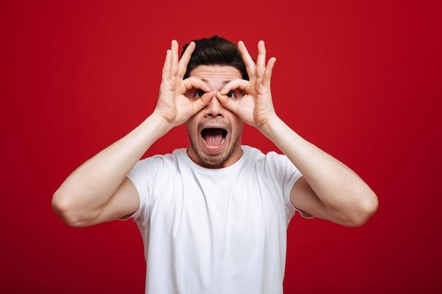 Портрет счастливого молодого человека в белой футболке указывая