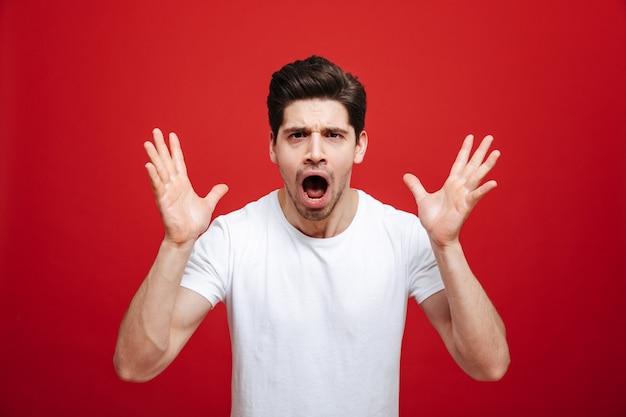 Портрет потрясенного молодого человека в белой футболке