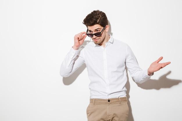 サングラスの下をよそ見し、影のある白いスペースに手で身振りで示すシャツに身を包んだ剃っていないブルネットの男