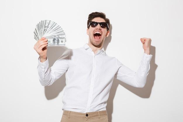 Эмоциональный брюнет парень в рубашке и солнцезащитные очки, крича с кулак, держа денежный приз в наличных, изолированных на белой стене с тенью