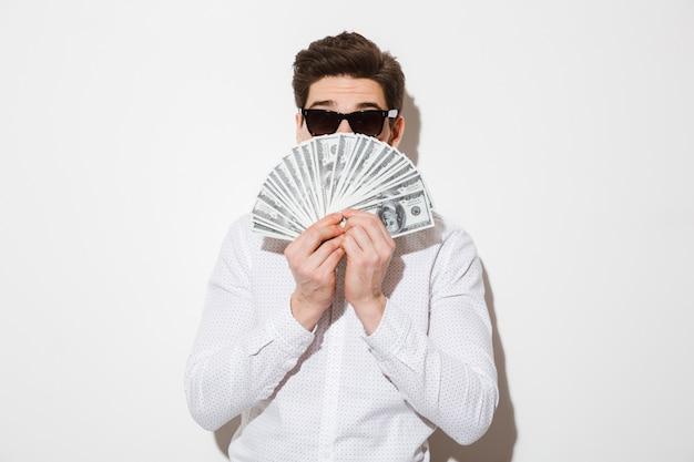 Фотография забавного человека в повседневной рубашке и солнцезащитных очках, закрывающего лицо веером денег в долларовой валюте, изолированных на белой стене с тенью