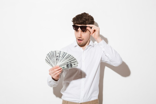 Фотография удивленного счастливчика в рубашке, снимающего черные очки и смотрящего на веер долларовых банкнот с волнением, изолированного над белой стеной с тенью