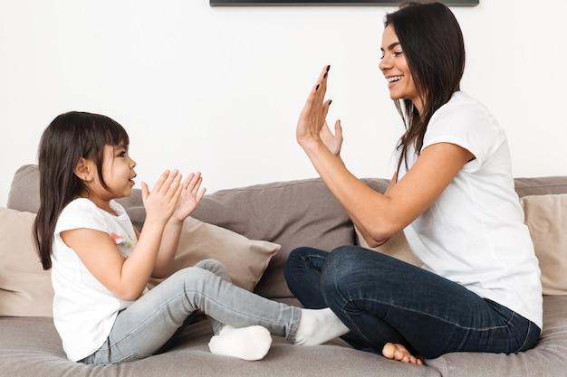 Портрет веселый семейный мать и девушка, играя вместе пирожок пирог, сидя на диване в квартире