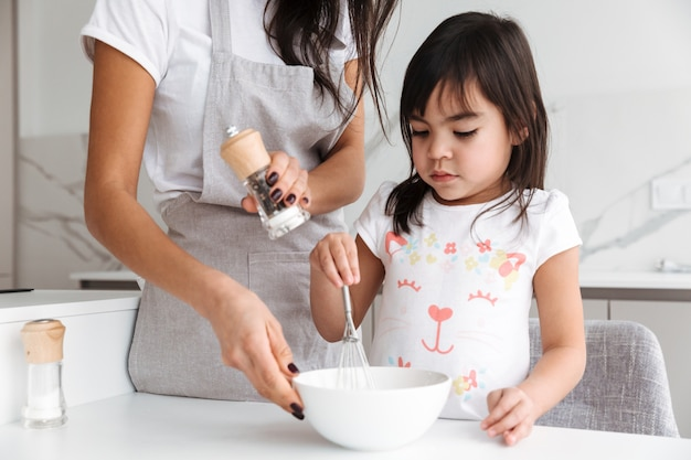 自宅のキッチンで、手動ミキサーを使用して一緒に料理をする彼女の小さな娘とエプロンの主婦の写真のクローズアップ