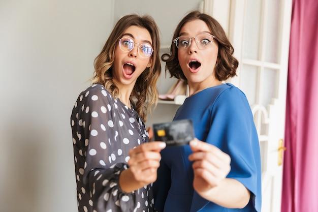 ショックを受けた若い女性の買い物中毒者はクレジットカードを示します。