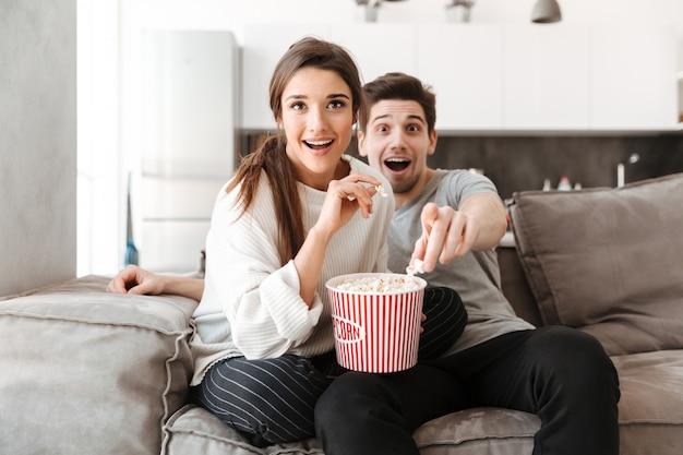 ソファでくつろいで興奮している若いカップルの肖像画