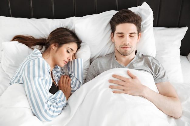 一緒に寝ている素敵な若いカップルの肖像画