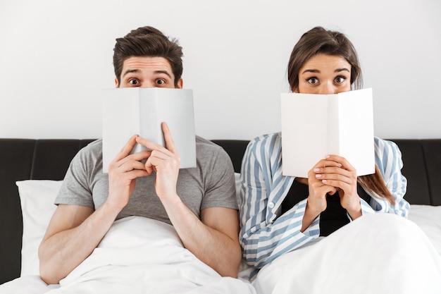 Счастливая милая пара держа книги пока сидящ совместно