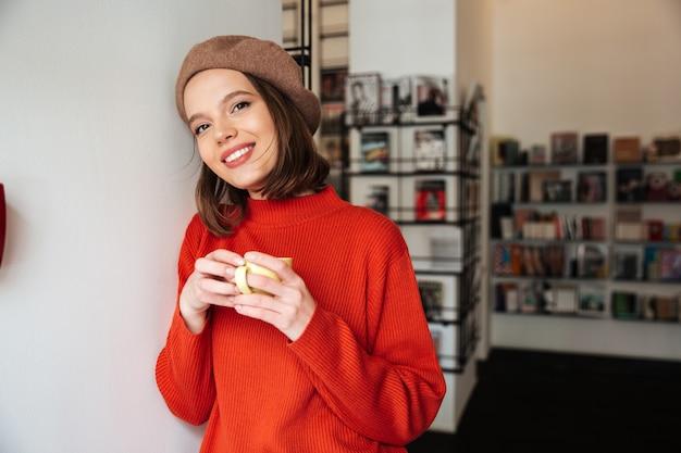 Портрет улыбающейся девушки, одетой в свитер