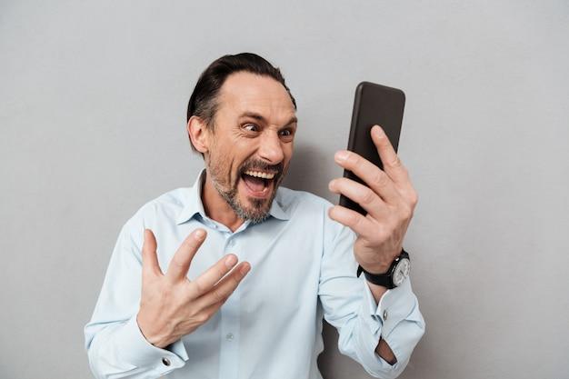 Портрет яростного зрелого человека, одетого в рубашку