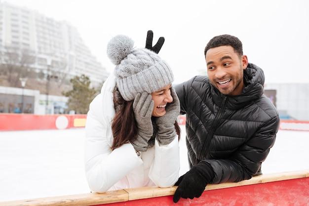 Счастливые смешные любящие пары кататься на коньках на катке на открытом воздухе.