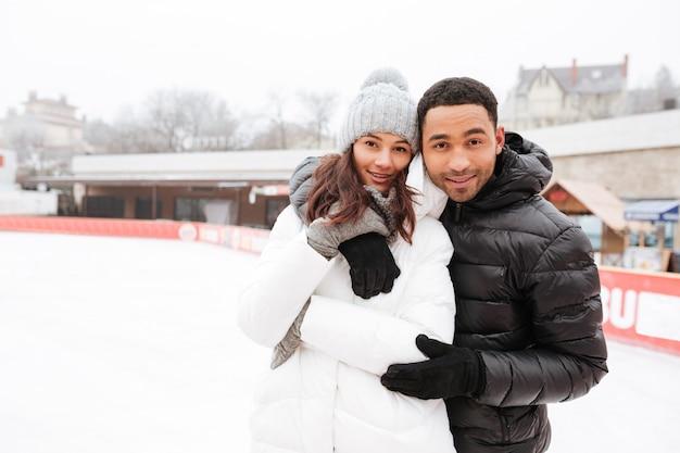 Улыбаясь влюбленная пара на коньках на катке на открытом воздухе.