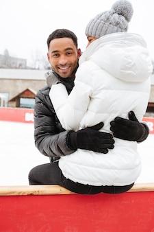 Счастливые влюбленные на коньках на катке на открытом воздухе.